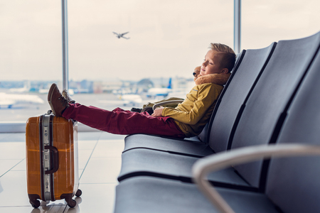 I need to rest before flight. Little boy sleeping while sitting in airport lounge with his feet on suitcase Stock Photo