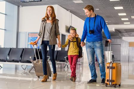Lassen Reise beginnen. Portrait des netten Paar mit ihrem Sohn am Flughafen zu Fuß nach unten Flur mit Koffern