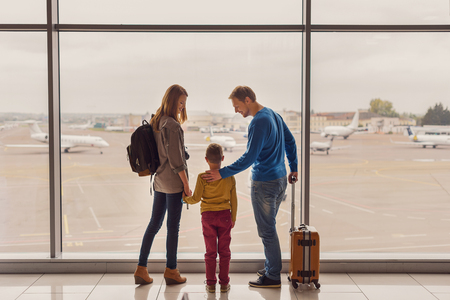 let out: Let is fly. Back view shot of happy parents travelling with their little son looking out window at airport terminal