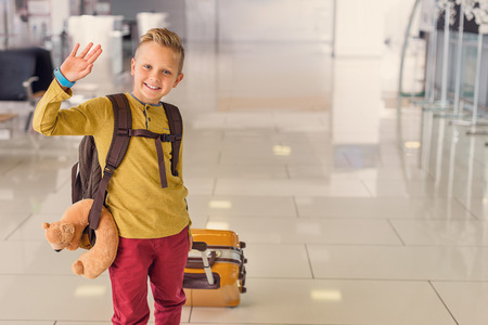 Hello everyone. Cropped shot of cute little boy waving and looking at camera, smiling while being at airport