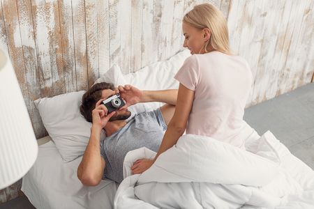 Joyful young man is lying on bed and photographing his girlfriend. Woman is sitting and smiling