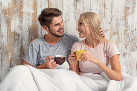 You are my love. Cute young loving couple is sitting in bed and smiling. Man is holding cup and touching female hair with gentleness
