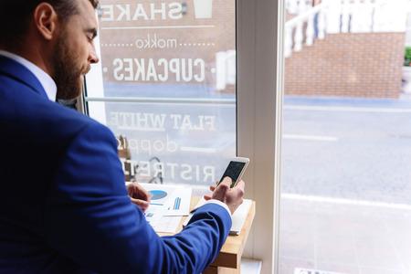 businesslike: businesslike man in costume looking into his smartphone indoors