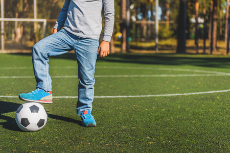 aspirational: Close up of boy legs standing near ball with preparation on field Stock Photo