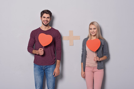I plus you equals love. Happy young man and woman are standing and holding heart cards. They are looking at camera and smiling Stock Photo