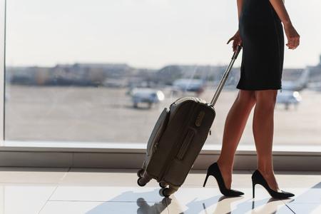 Sluit omhoog van benen van elegante vrouw die op zakenreis gaan. Ze staat op het vliegveld en draagt ??een koffer Stockfoto