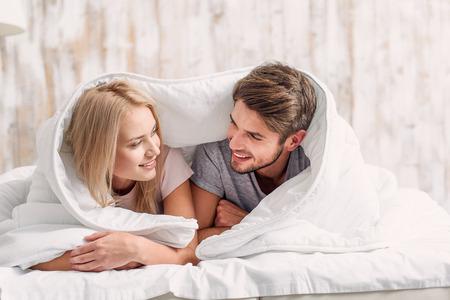 Het gelukkige jonge houdende van paar ligt op bed dat door deken wordt behandeld. Ze kijken elkaar aan met liefde en glimlachen