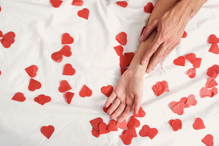 gentleness: Valentine day. Close up of man touching female hand with gentleness on bed with small hearts
