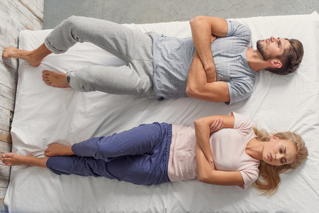 lovers quarrel: Offended couple is lying on bed with sadness. Man and woman are crossed arms with mistrust