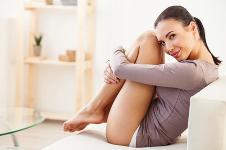 hugging legs: Happy young woman is resting at home with pleasure. She is hugging her smooth bare legs and smiling. Girl is sitting on couch and looking at camera with satisfaction