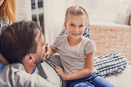 cropped shot: Cropped shot of cute little girl sitting beside her father, looking at camera and smiling Stock Photo