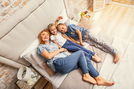 tenderly: My family is my home. Top view shot of happy smiling mother lying on bed with her two children and embracing them tenderly Stock Photo