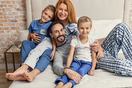 sitt: Happy family sitting in bedroom on bed and posing at camera, smiling sincerely