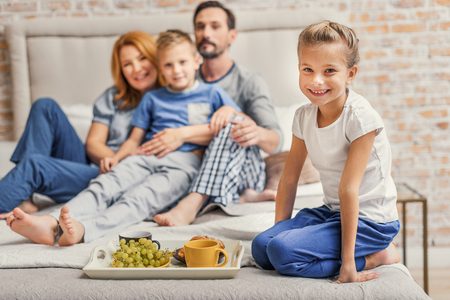 cup four: Photo of beautiful little girl sitting on bed next to tray of food with her happy family on background Stock Photo