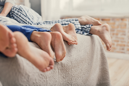 Enjoying some family time. Close up of family showing off four feet and lying on bed in morning