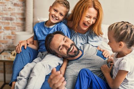 young smiling family of four having fun while lying on bed and hugging each other