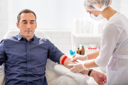 healthy looking: Skillful nurse is doing blood test for man in clinic