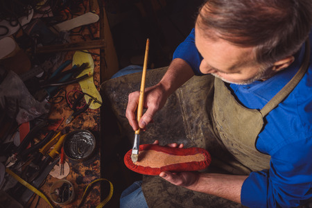 bootmaker holding a brush with a footwear while sitting at the desk