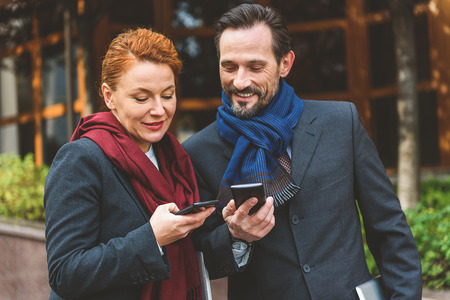 Middle-aged man and woman are exchanging phone numbers. They are standing on street and laughing Stock Photo