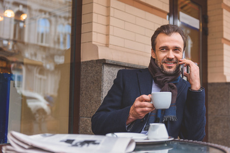 Cheerful man is resting in cafe outdoors. He is talking on phone and holding cup. Man is sitting at table near newspaper and smiling