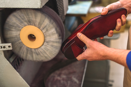 atelier: luxury red shoe heel grinding inside an atelier, close up