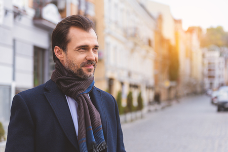Joyful man is standing on street with relaxation. He is looking aside and smiling Stock Photo