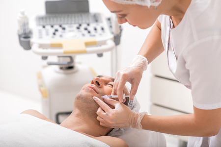 soustředění: Professional doctor is injecting botox near male mouth with concentration. Beauty and anti-aging concept
