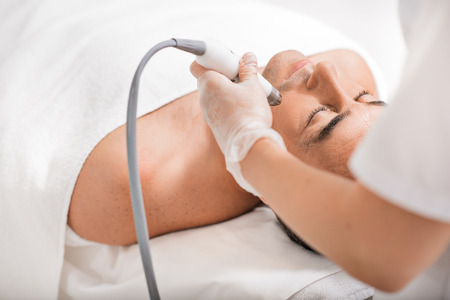 rejuvenating: Professional beautician is rejuvenating male face by cavitation laser apparatus. Man is lying on massage table and relaxing
