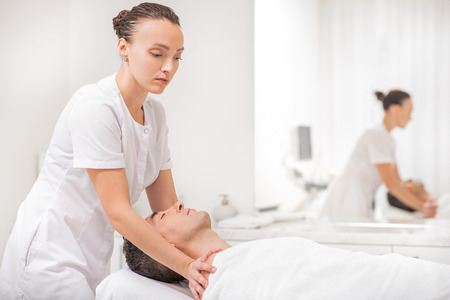 masseuse: Skillful masseuse is massaging male shoulders carefully. Man is lying and relaxing Stock Photo