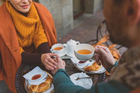 L'uomo e la donna felici stanno datando in mensa all'aperto. Si tengono per mano e bevono tè