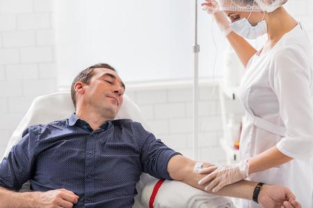 hombre de mediana edad está teniendo procedimiento por vía intravenosa en el hospital. Él está sentado y relajante. La enfermera está poniendo cuidadosamente gotero