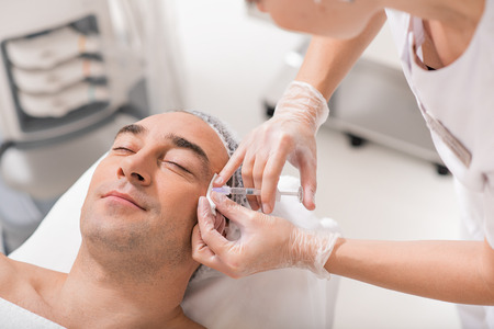 Middle-aged man is getting facial botox injection in clinic. He is lying and smiling Stock Photo