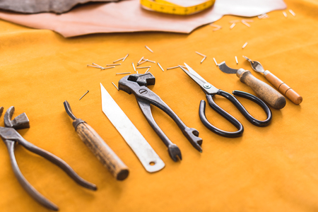 neatly arranged tools of an artisan lying on yellow fabric, angle view Stock Photo