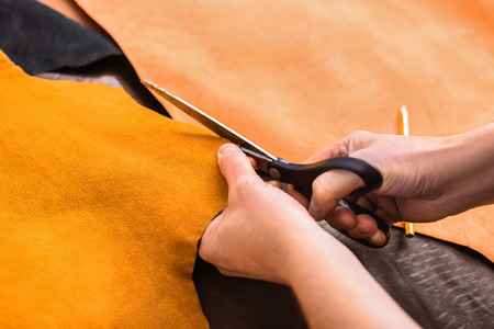 cutting of a yellow leather with tailors scissors, close up Stok Fotoğraf