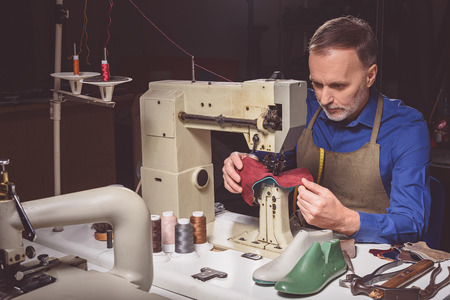 atelier: bootmaker sews leather boots on a tailoring machine at the atelier