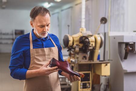 Propietario de una pequeña empresa como taller de mirar zapato Foto de archivo - 65747417