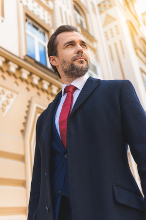 steadfast: Confident businessman is standing in city. He is looking aside pensively Stock Photo
