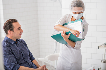 Man is visiting doctor in clinic. He is sitting and smiling. Woman is standing and holding documents Stock Photo