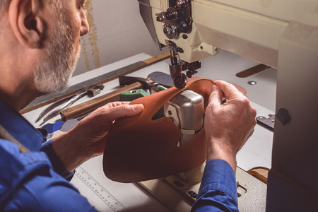 operates: handyman operates an industrial sewing machine in a shoe factory, close up Stock Photo