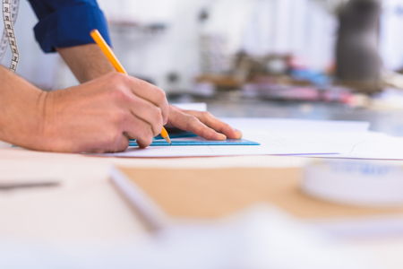 creator: side view of a creator drawing on a table in the atelier Stock Photo