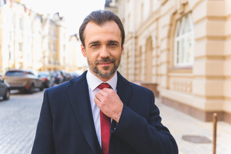 Confident man is standing on street and adjusting his tie. He is smiling