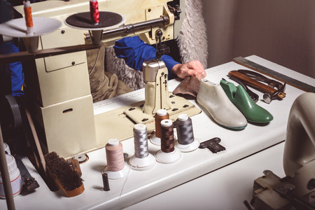 msn: sewing machine with thread reels and a man preparing to sew, close up