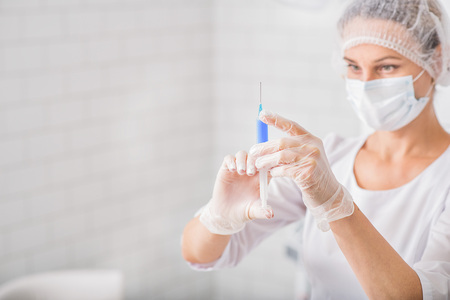 Serious female doctor is preparing syringe with blood. She is standing and looking at it with concentration