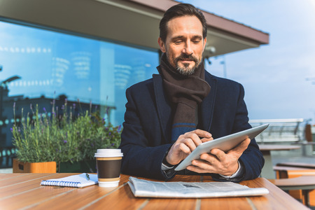 sitt: Joyful businessman is using tablet on coffee break. He is sitting at table in cafeteria outdoors and smiling Stock Photo