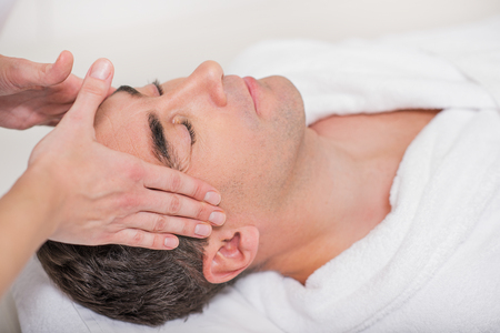 masseuse: Close up of masseuse hands massaging male head at spa. Man closed eyes with enjoyment