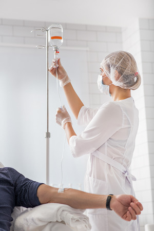 female catheter: Professional doctor is putting drip for patient. She is standing and looking at medical liquid with seriousness
