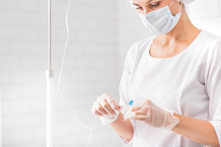 female catheter: Professional serious doctor is preparing catheter for drop counter