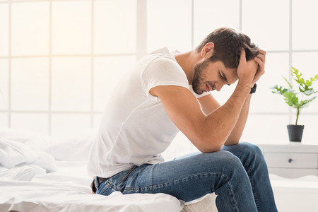 What a horrible pain. Desperate man touching head with anxiety. He is sitting on bed at home