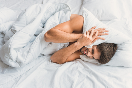 vexation: What a noise. Man is lying on bed under blanket and pressing pillow to his head. Male is screwing up his eyes