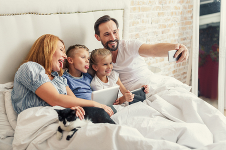 One photo for album. Happy smiling middle-aged parents and their kids taking selfie at bedroom while staying in bed Banco de Imagens - 66011133